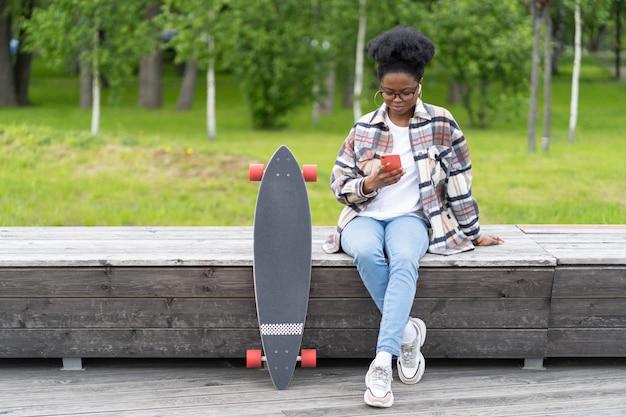 Une jeune fille africaine discute à l'aide d'une application pour smartphone assise à l'extérieur avec un skate longboard dans un parc