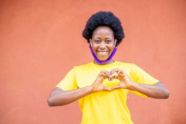 Jeune fille africaine noire portant un masque protecteur en tissu sous son nez dans la pandémie de coronavirus covid19