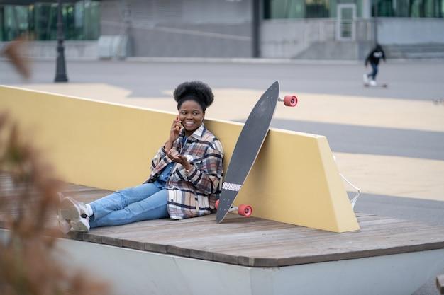 Une jeune fille africaine parle au téléphone s'assoit avec un longboard dans un skate park urbain communique sur son mobile