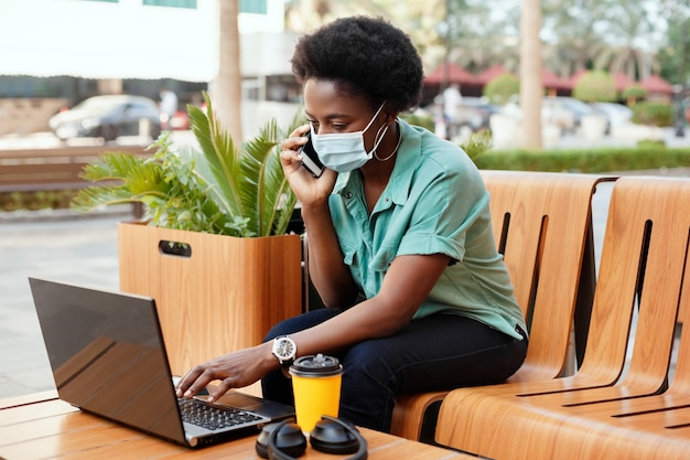 Une jeune fille africaine portant un masque médical parle au téléphone et travaille avec un ordinateur portable à une table dans un café. distanciation sociale et travail, travail en ligne, affaires en ligne.