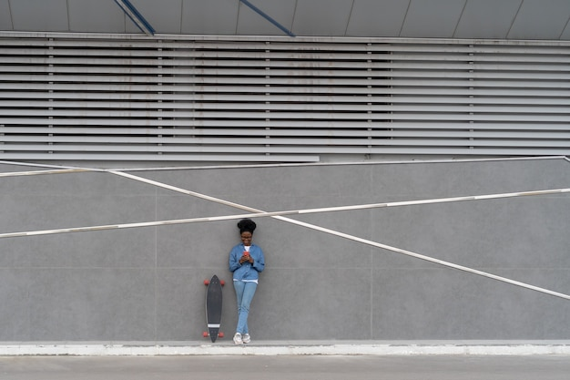 Une jeune fille africaine réfléchie tient un smartphone concerné par la lecture de l'application de téléphone portable envoyée par courrier électronique
