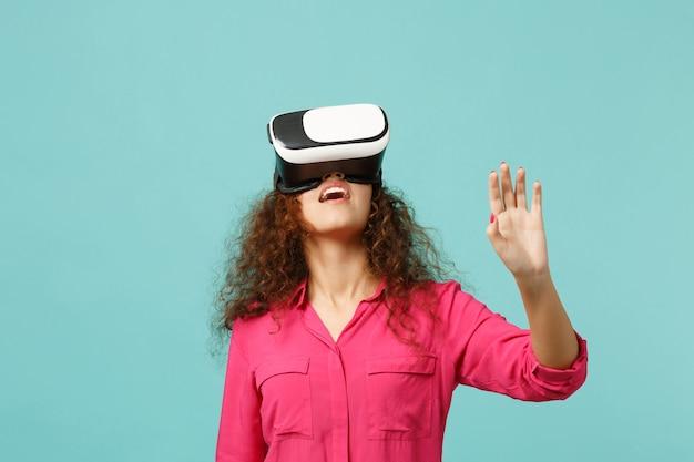 Jeune fille africaine regardant dans un casque, touchez quelque chose comme appuyer sur le bouton, pointant sur un écran virtuel flottant isolé sur fond bleu turquoise. les gens émotions sincères, concept de style de vie.