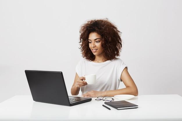 Jeune fille africaine tenant la tasse en regardant portable souriant sur mur blanc.