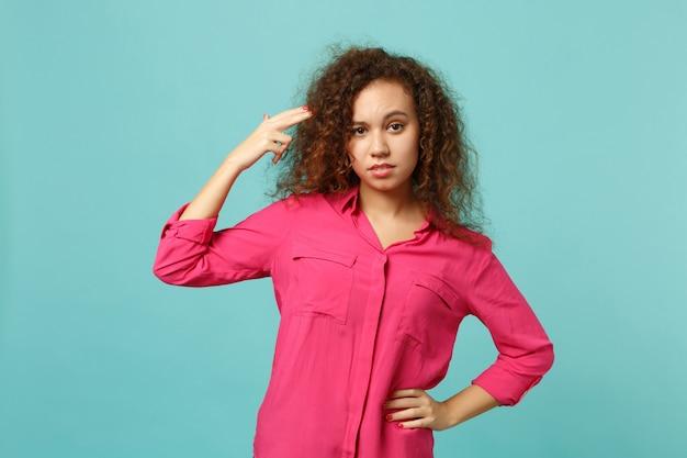 Une jeune fille africaine en vêtements décontractés pointe du doigt la tête comme si elle s'apprêtait à se tirer isolée sur un fond de mur bleu turquoise. les gens émotions sincères, concept de style de vie. maquette de l'espace de copie.