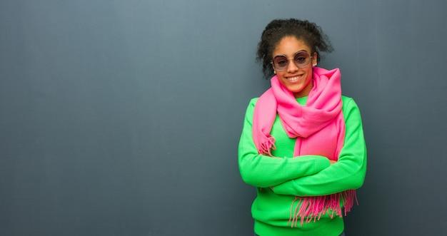 Jeune fille afro-américaine aux yeux bleus croisant les bras, souriante et détendue