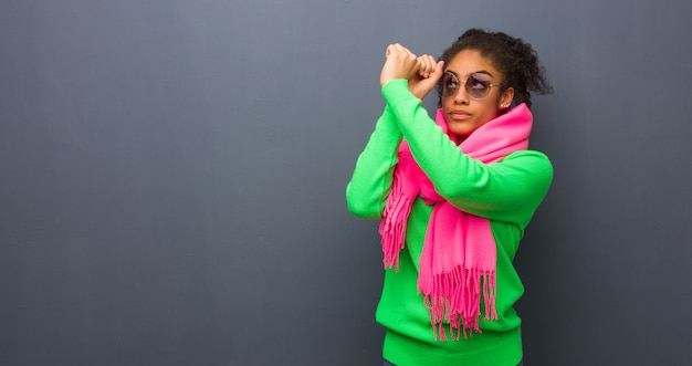 Jeune fille afro-américaine aux yeux bleus faisant le geste d'une longue-vue