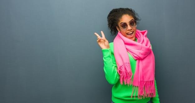Jeune fille afro-américaine aux yeux bleus faisant un geste de victoire