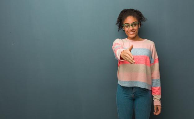 Jeune fille afro-américaine aux yeux bleus tendre la main pour accueillir quelqu'un