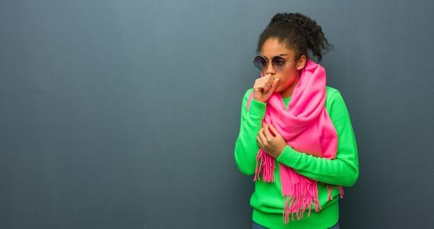 Jeune fille afro-américaine aux yeux bleus toussant, malade à cause d'un virus ou d'une infection