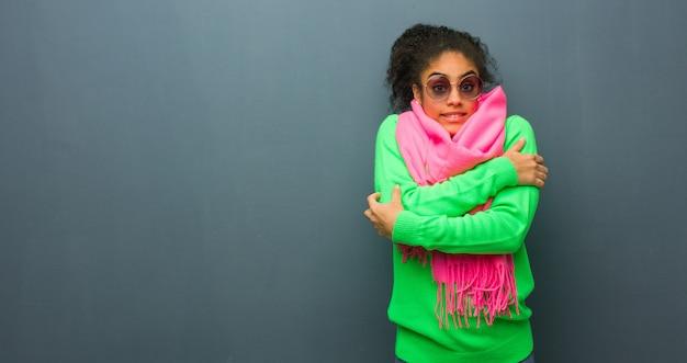 Jeune fille afro-américaine aux yeux bleus va froid en raison de la basse température