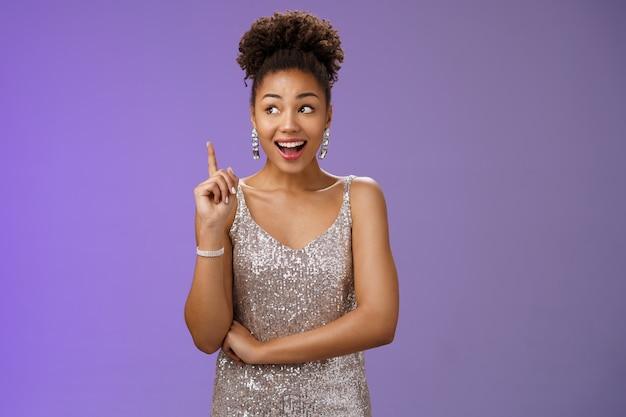 Jeune fille afro-américaine créative et rêveuse en robe argentée lève l'index geste eureka regarde de côté inspiré a une idée géniale suggestion de partage dire plan à haute voix, debout sur fond bleu.