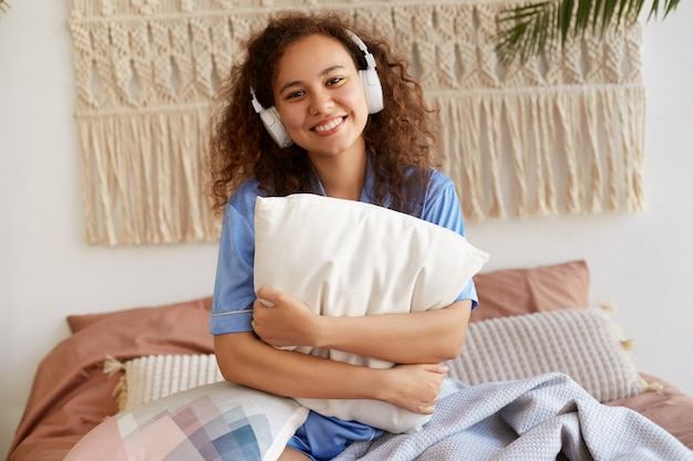 Jeune fille afro-américaine frisée joyeuse, implantée sur le lit, serrant un oreiller, écoutant la chanson préférée dans les écouteurs, souriant largement et a l'air heureux.