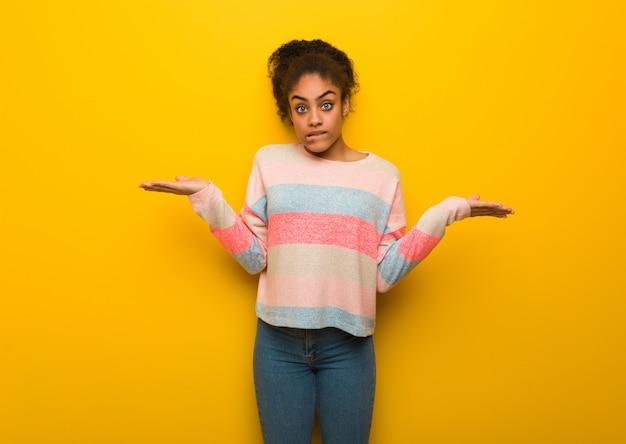 Jeune fille afro-américaine noire aux yeux bleus confuse et douteuse
