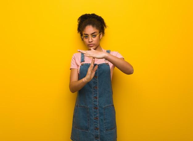 Jeune fille afro-américaine noire aux yeux bleus, faisant un geste de délai d'attente