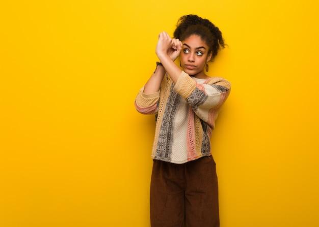 Jeune fille afro-américaine noire aux yeux bleus faisant le geste d'une longue-vue