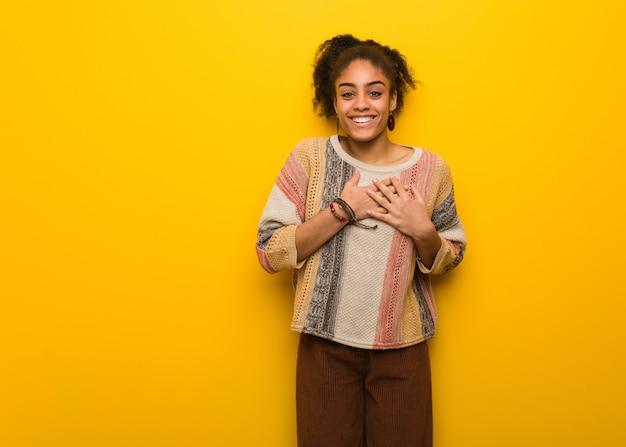 Jeune fille afro-américaine noire aux yeux bleus faisant un geste romantique