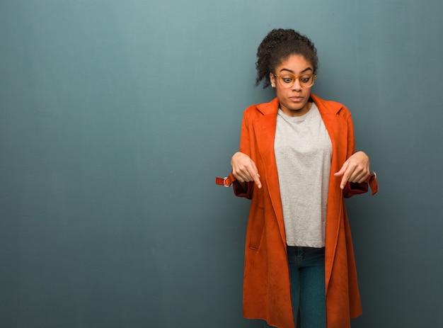Jeune fille afro-américaine noire aux yeux bleus pointant vers le bas