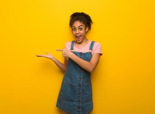 Jeune fille afro-américaine noire aux yeux bleus tenant quelque chose avec la main