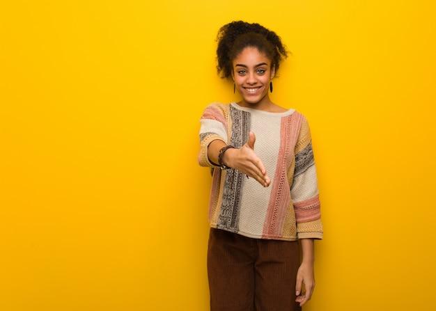 Jeune fille afro-américaine noire aux yeux bleus tendre la main pour accueillir quelqu'un
