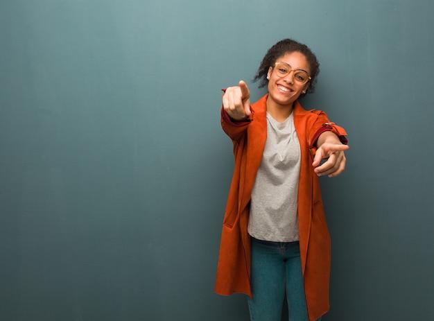 Jeune fille afro-américaine noire avec des yeux bleus joyeux et souriant