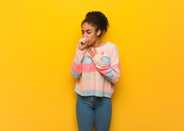 Jeune fille afro-américaine noire avec des yeux bleus toussant, malade en raison d'un virus ou d'une infection