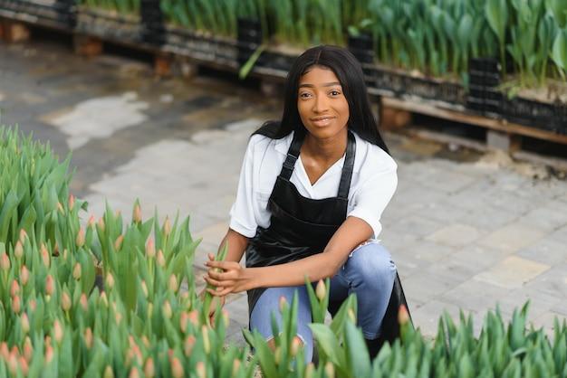 Jeune fille afro-américaine, ouvrière avec des fleurs en serre.
