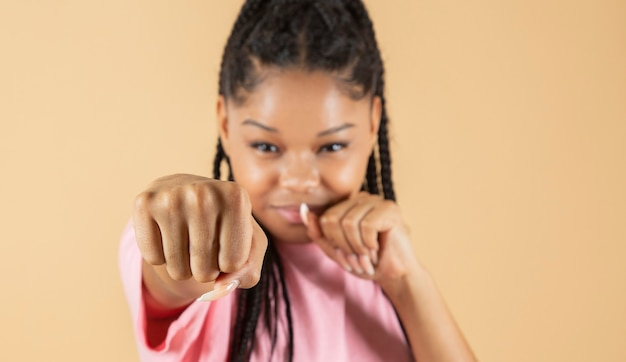 Jeune fille afro-américaine portant des vêtements décontractés frappant le poing pour se battre, attaque agressive et en colère, menace et violence