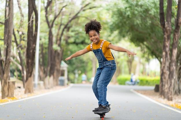 Jeune fille afro-américaine s'amusant à faire de la planche à roulettes à l'été en plein air.