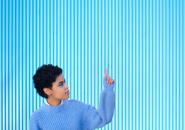 Jeune fille afro latina et pull décontracté sur le mur bleu, pointant la main et le doigt sur le côté