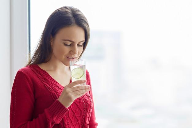 Jeune fille avec un aglass d'eau au citron vert