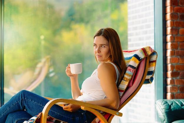 Une jeune fille agréable avec un regard pensif profite d'une belle journée assise dans un fauteuil à bascule avec une tasse de son café préféré.
