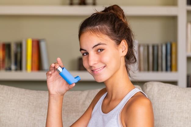 Jeune fille à l'aide d'un inhalateur assis dans un canapé à la maison