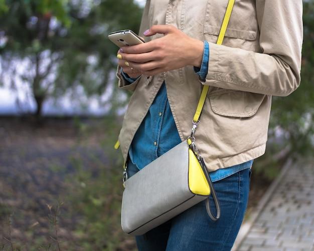 Jeune fille à l'aide d'un téléphone portable dans la rue