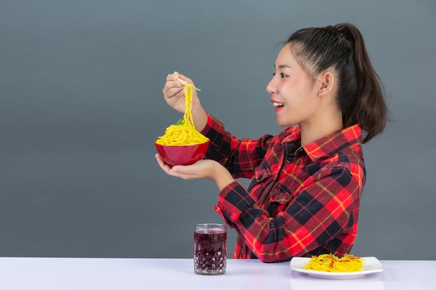 Jeune fille aime manger des spaghettis à la maison