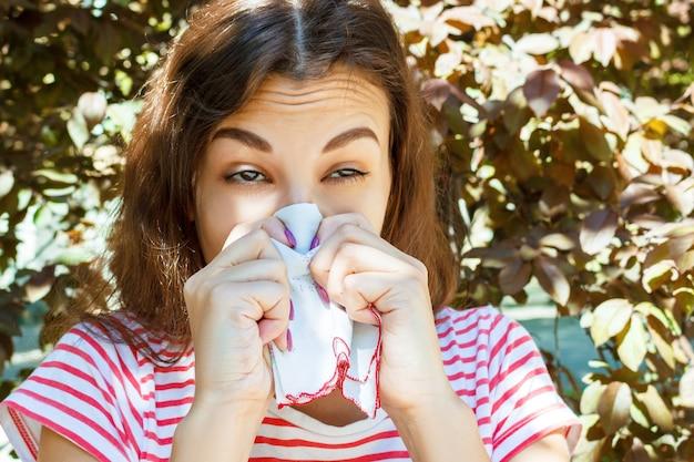 Jeune fille allergique au parc en automne. une fille qui éternue se mouche dans une serviette.