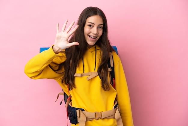 Jeune fille d'alpiniste avec un grand sac à dos d'isolement comptant cinq avec des doigts
