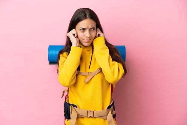 Jeune fille d'alpiniste avec un gros sac à dos isolé sur fond rose frustré et couvrant les oreilles