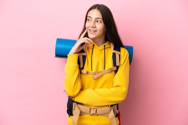 Jeune fille d'alpiniste avec un gros sac à dos isolé sur fond rose pensant à une idée tout en levant les yeux