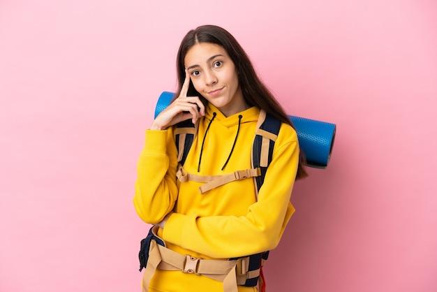 Jeune fille d'alpiniste avec un gros sac à dos isolé sur fond rose en pensant à une idée