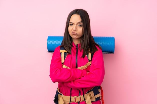 Jeune fille d'alpiniste avec un gros sac à dos sur un mur rose isolé se sentant bouleversé