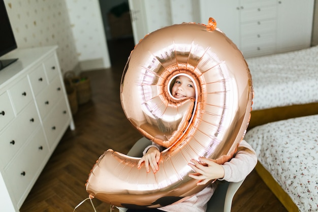 Jeune fille d'anniversaire jolie visage à travers le trou dans le ballon
