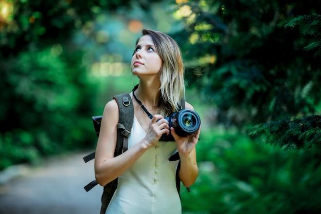 Jeune fille avec un appareil photo et un sac à dos dans le parc