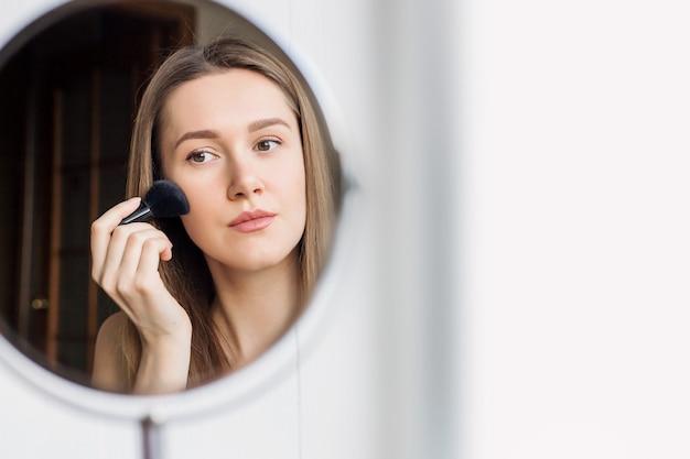 Une jeune fille d'apparence caucasienne se regarde dans un miroir rond et se maquille, rougit avec un pinceau. une fille est assise dans une pièce et applique quotidiennement ses soins du visage et son maquillage.