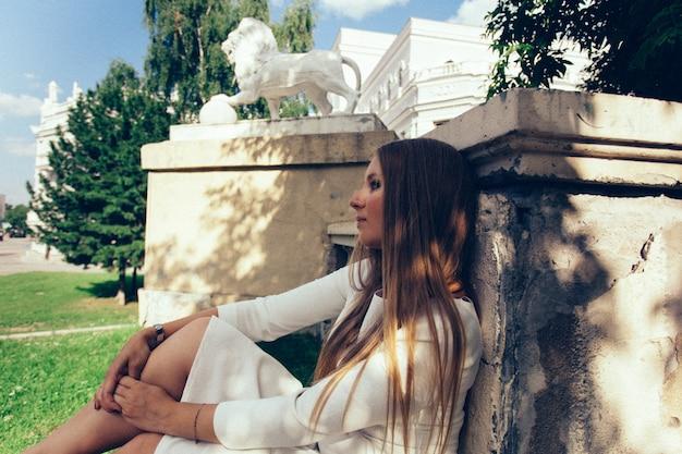 Jeune fille d'apparence européenne dans une robe blanche sur le fond du bâtiment.