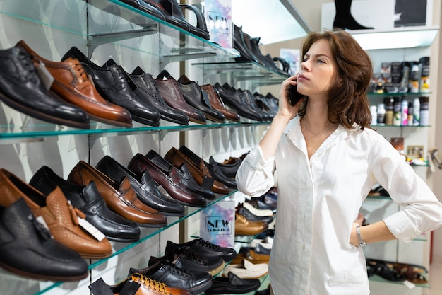 Une jeune fille appelle et conseille d'acheter des chaussures pour hommes.