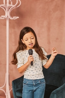 Jeune fille apprenant à chanter à la maison