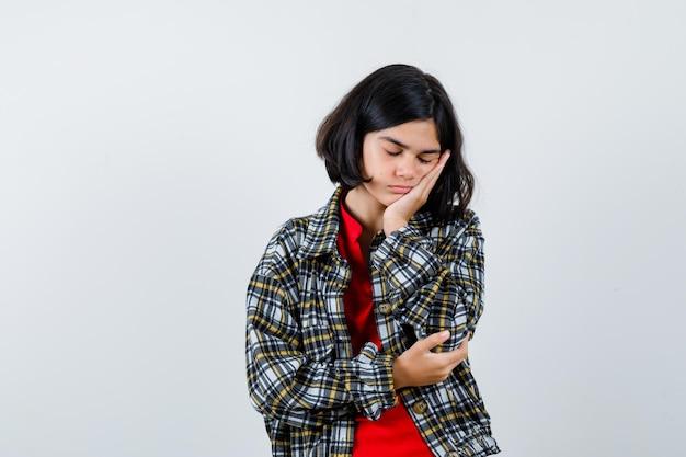 Jeune fille appuyée sur la joue de la paume, faisant semblant de dormir en chemise à carreaux et t-shirt rouge et ayant l'air endormie, vue de face.