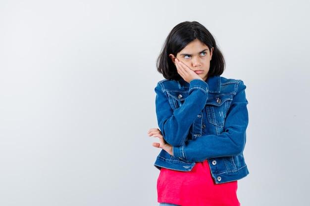 Jeune fille appuyée sur la joue de la paume, pensant à quelque chose en t-shirt rouge et veste en jean et l'air songeur. vue de face.