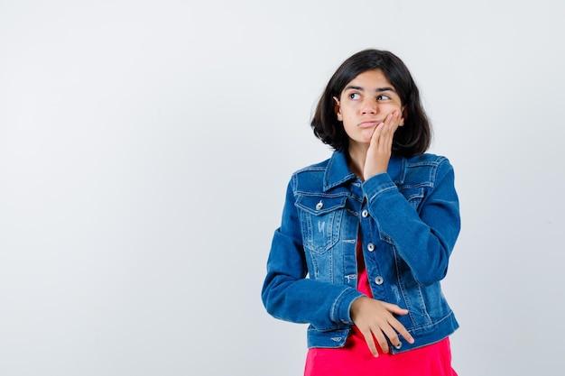 Jeune fille appuyée sur la joue de la paume, regardant loin en t-shirt rouge et veste en jean et regardant pensive, vue de face.