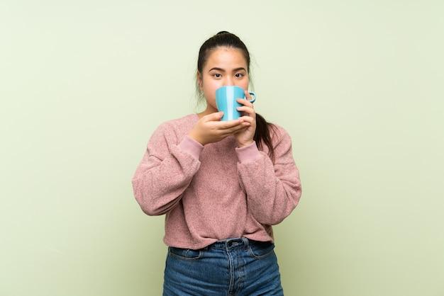 Jeune fille asiatique adolescente sur mur vert isolé, tenant une tasse de café